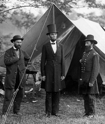 Abraham Lincoln standing outside tent with generals